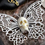 White metal butterfly with bone skull necklace